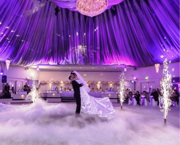 Groom lifting bride in smoky purple room