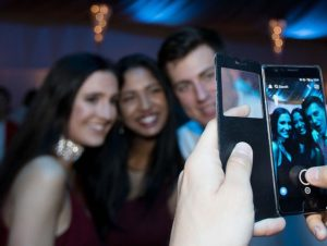 someone taking photo on phone camera or three party guests
