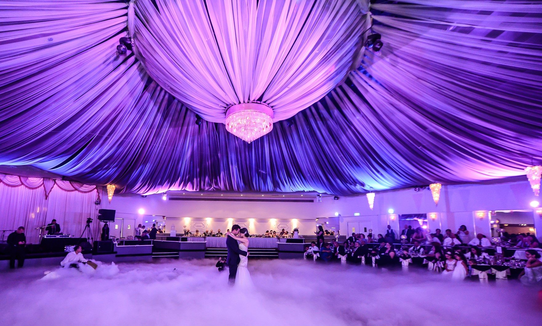 bride and groom dancing under canopy violet canopy in ballroom