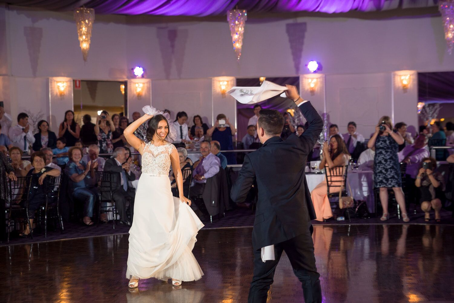 bride and groom dancing with guests looking on