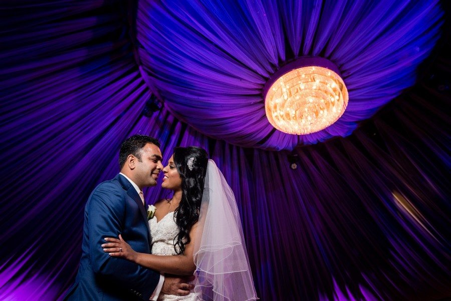bride and groom holding each other under blue canopy in ballroom