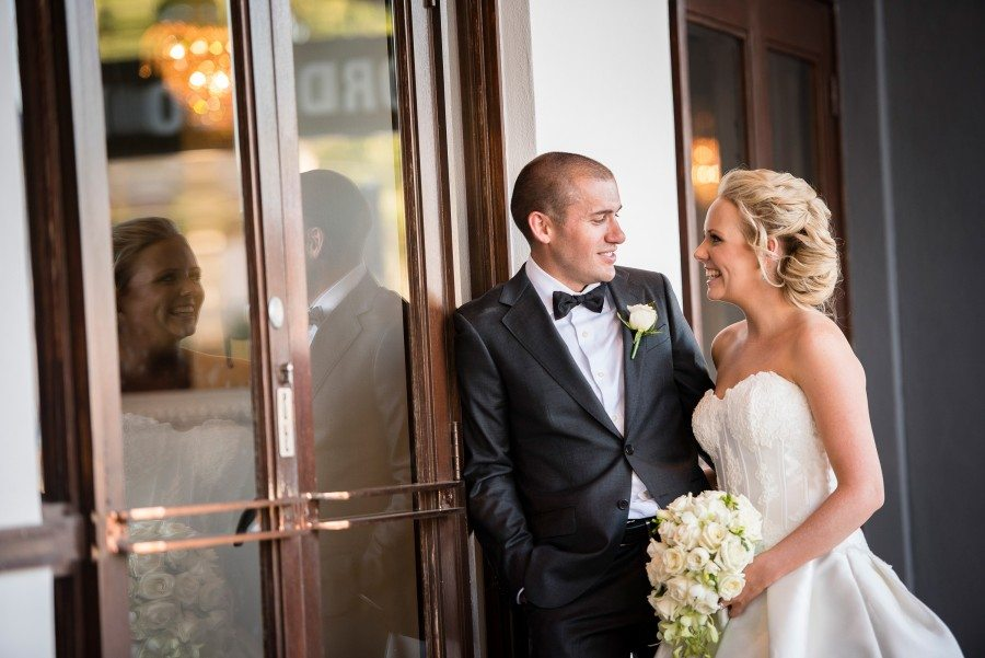 bride and groom against glass door