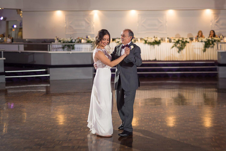bride dancing with older man in grey suit