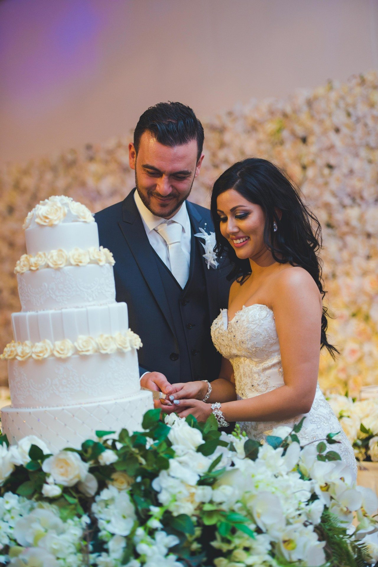 bride and groom cutting 4 tier white wedding cake