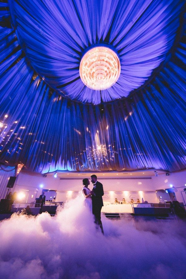 bride and groom dancing under blue canopy in ballroom