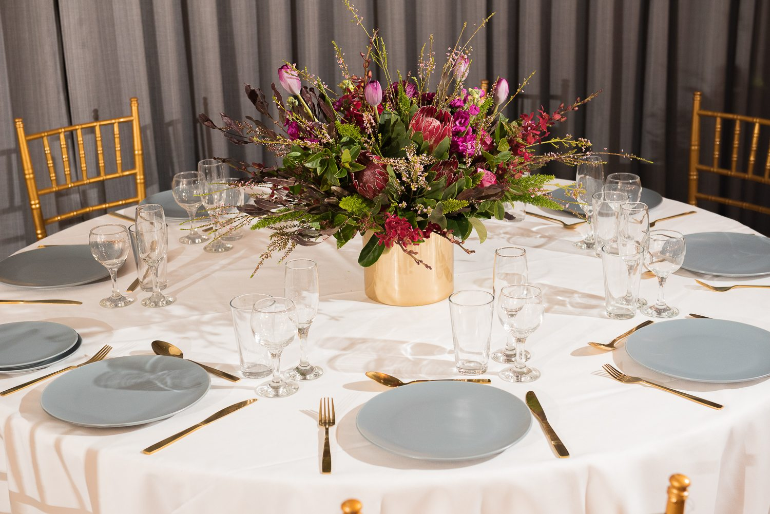 table setting with gold vase, bright flowers, grey plates and gold cutlery