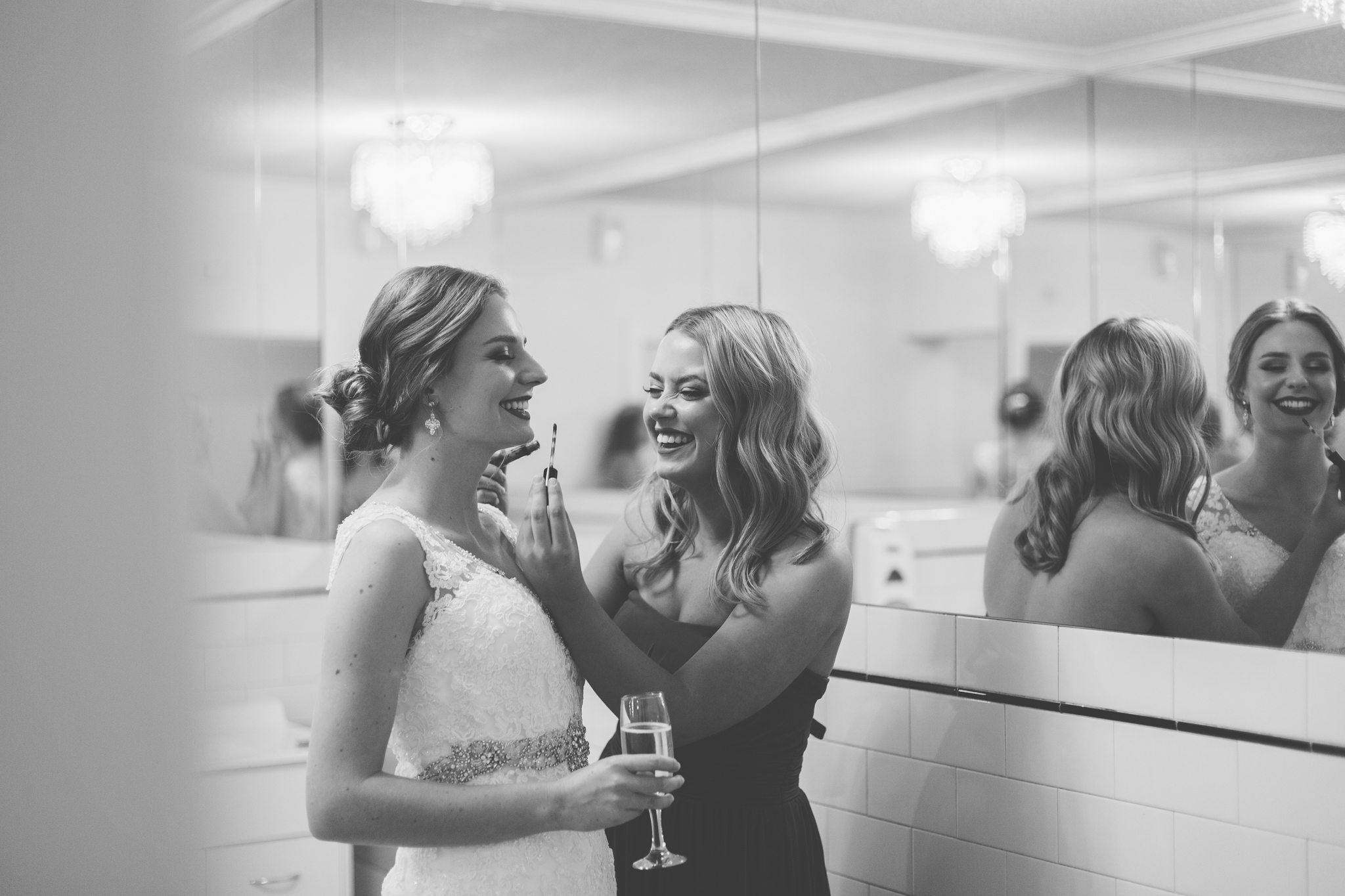 bride holding champagne wit friend putting lipstick for her surrounded by mirrors
