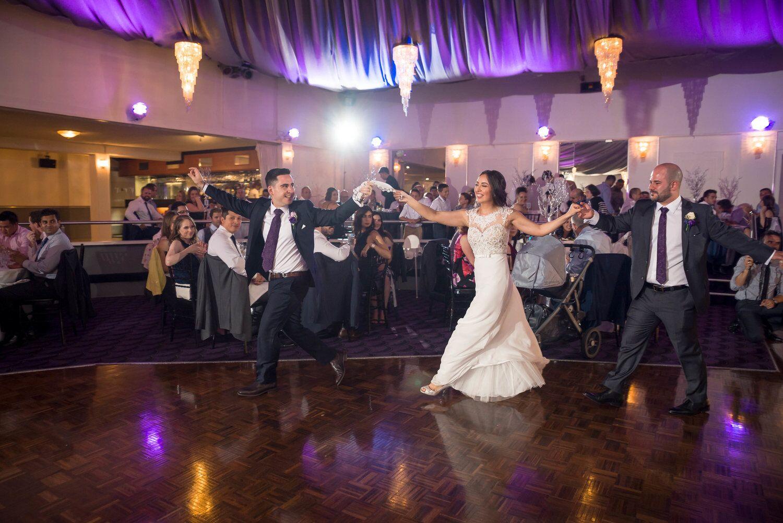 bride dancing with two men