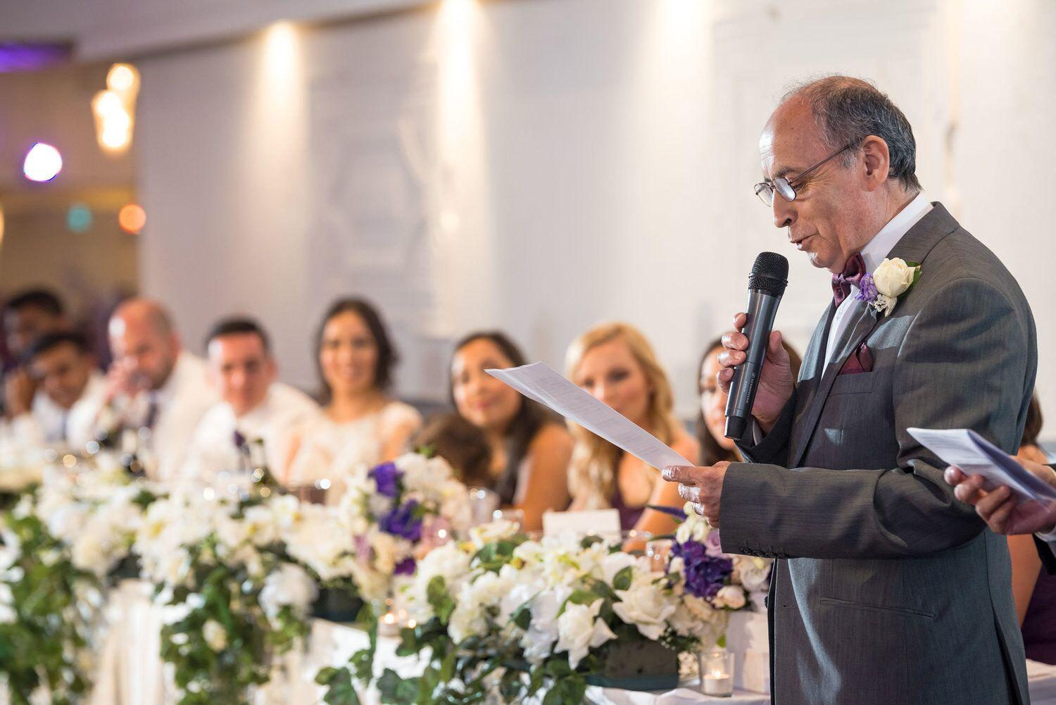 older man reading a speech with guests in background