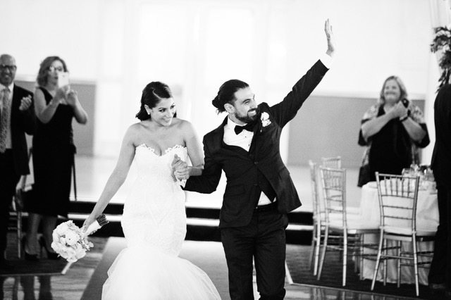 bride in white with groom waving to guests