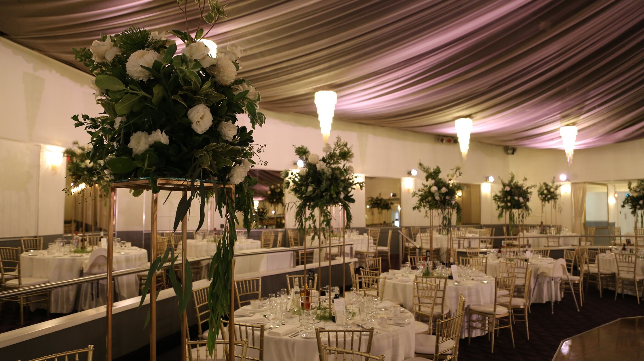 tall floral arrangement next to white draped tables set for dinner