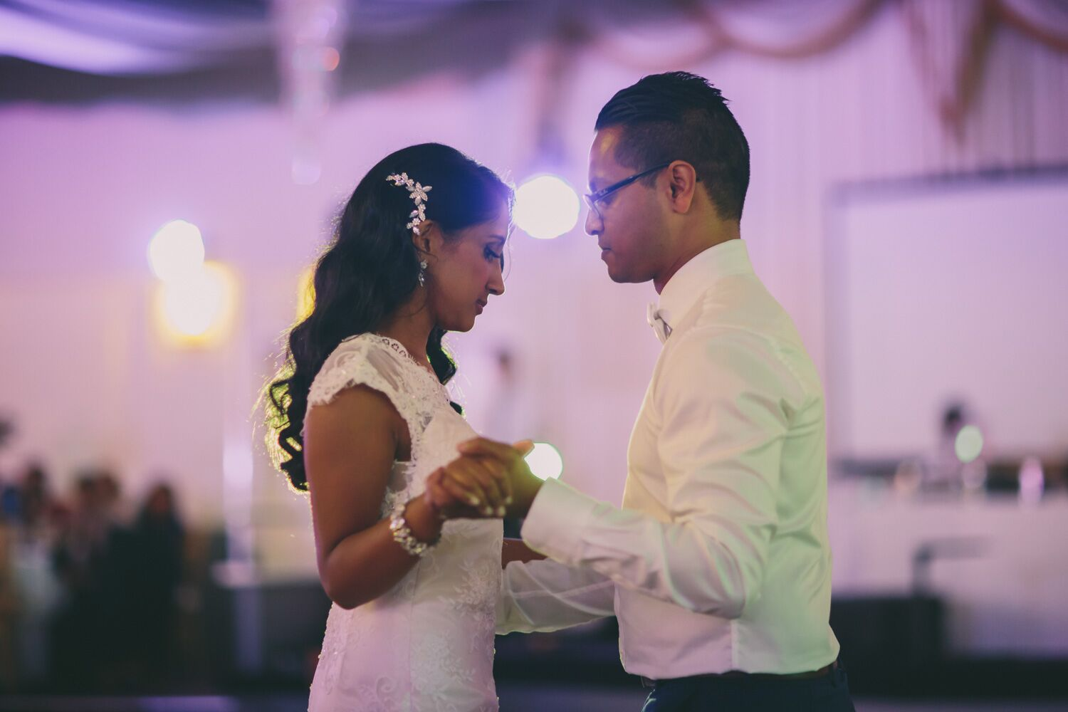 bride in white dancing with groom in white shirt
