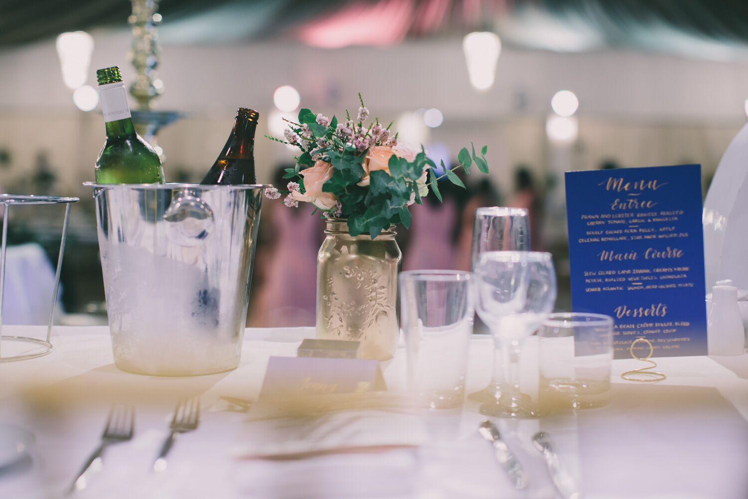 table setting with blue place card, gold bottle, and ice bucket with bottles