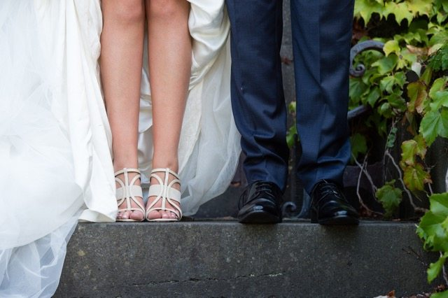 white strappy sandals on bride wearing white dress
