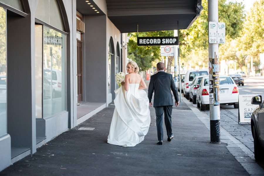 bride in white holding white flowers walking down street with man