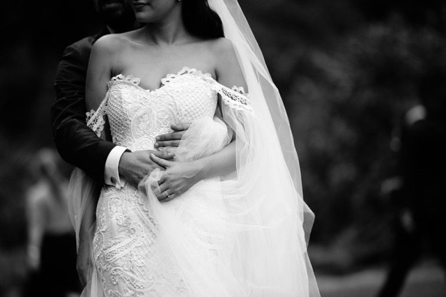 bride in white with grooms arms around her