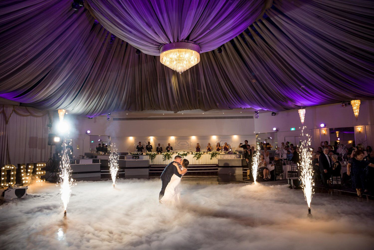 bride and groom under lighted canopy with fireworks in corners