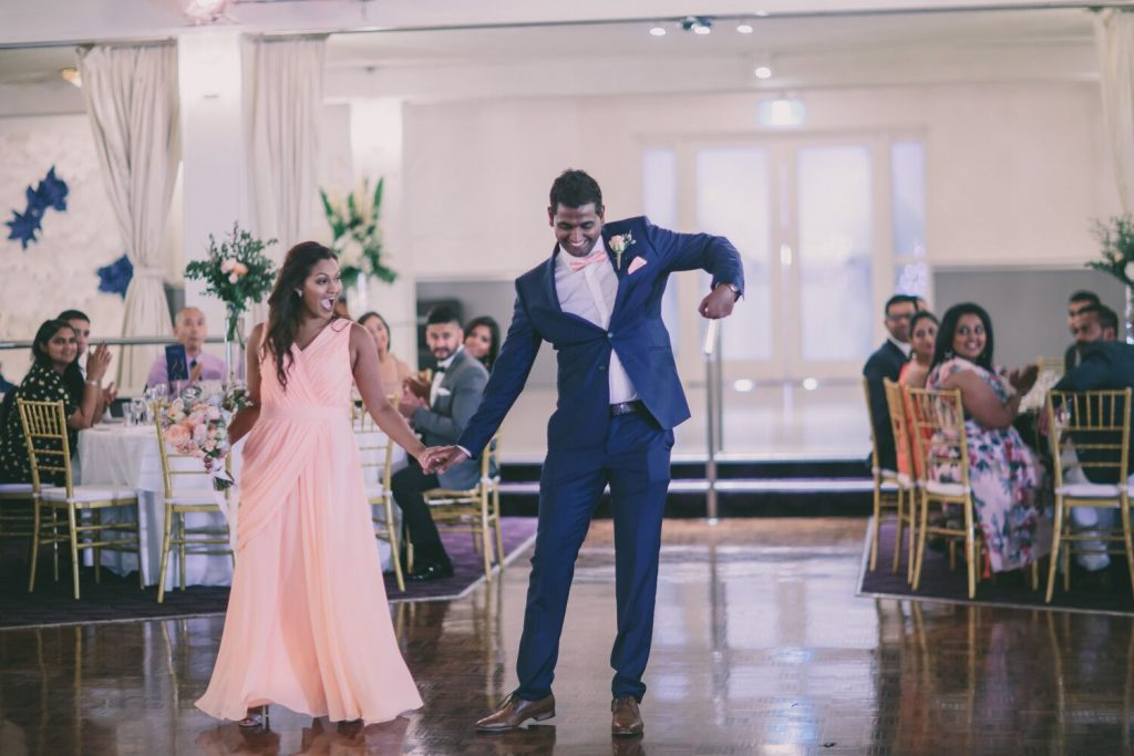 bride and groom dancing with guests in background