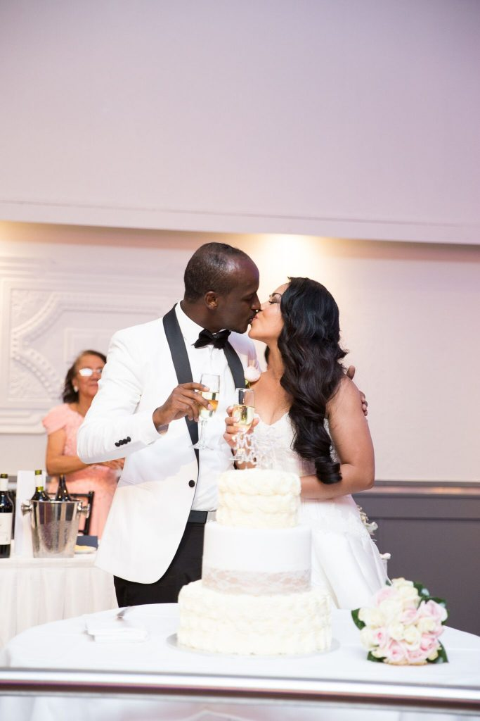 bride and groom kissing holding champagne behind cake
