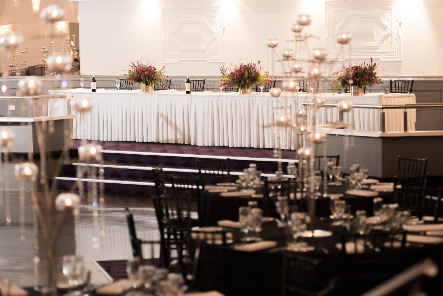 Main table with white cloth and guest tables with centrepiece