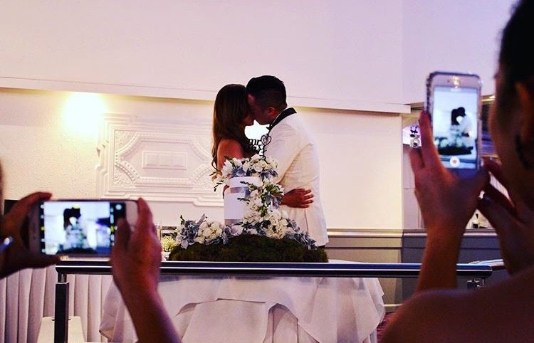 bride and groom behind cake kissing with guests taking photos