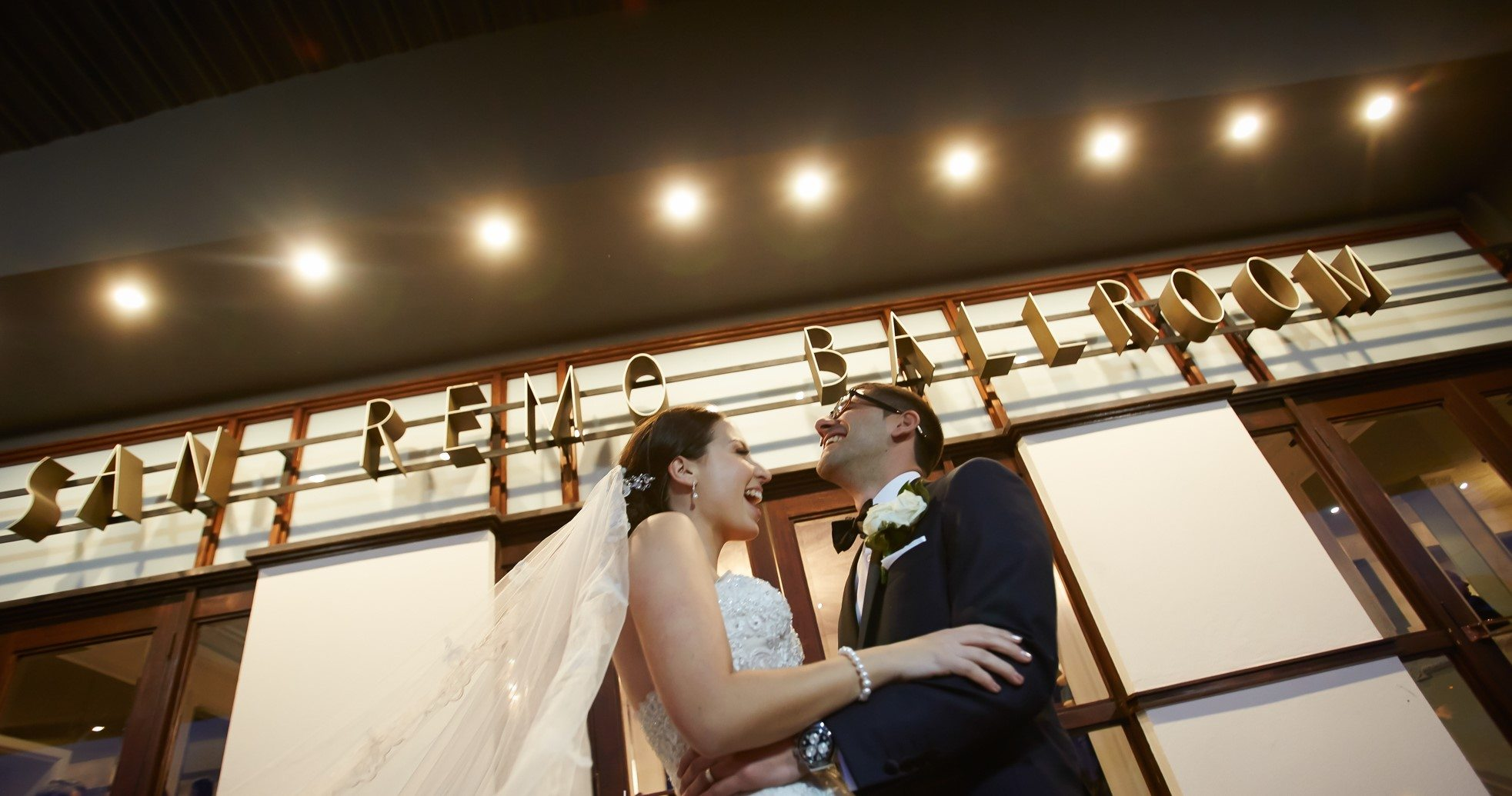 Bride and groom under lights and sign