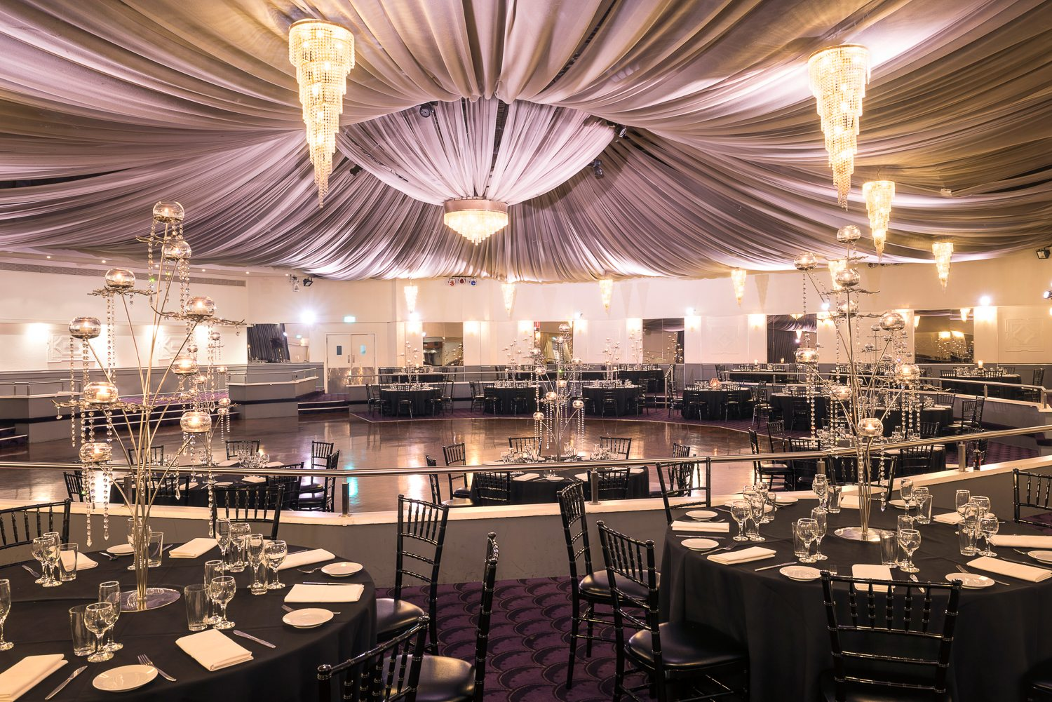 black tables, glass tableware and decoration in ballroom