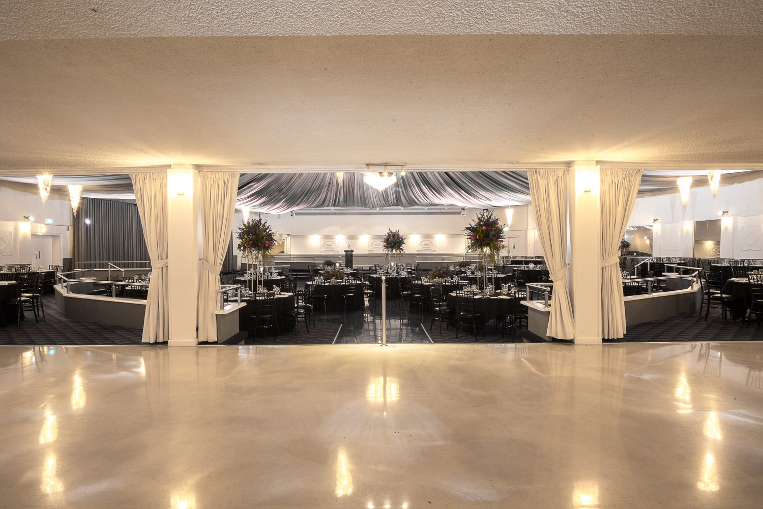 cream curtains bordering ballroom with black draped tables