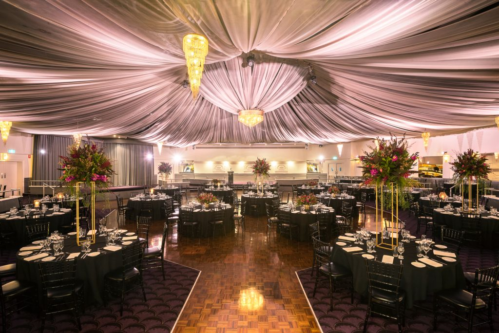 ballroom with mauve canopy, black draped tables and chairs