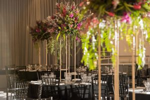 tall floral arrangement on black-draped table